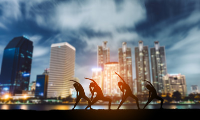 Young group man and woman yoga practice on mat relaxation in class exercise with pose fitness sport for healthy on the beach and seaside modern city building at night silhouette