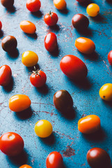 Variety of cherry tomatoes on blue background.