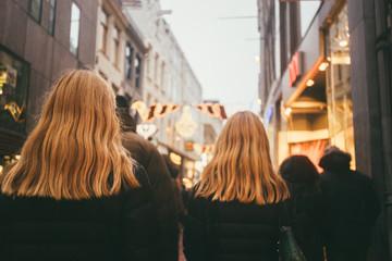 Two blonde women, walking on the commercial street,
