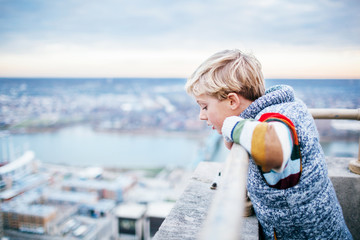 boy on top of a high building looks down at the city below