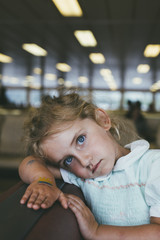 Tired four year old girl resting head on ferry boat seat