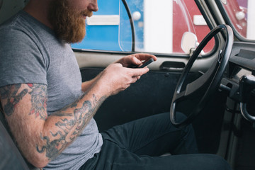 Young bearded man with tattoos texting with his cell phone in a vintage car