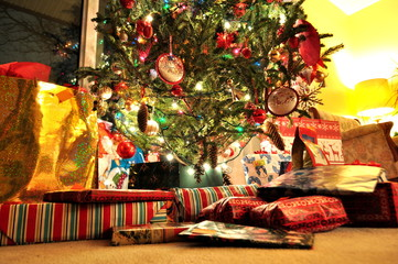 Decorated lit Christmas tree with wrapped presents and gift boxes underneath