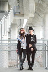 Two modern women standing under the bridge