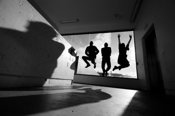 Three people jump in the stairwell of a parking garage, backlit by a bright window