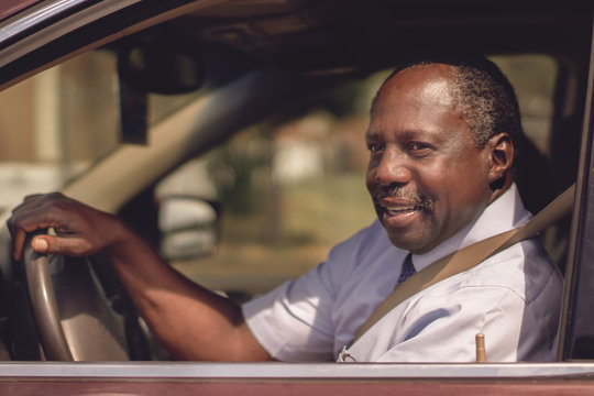 Black happy man in his early 60s driving a car