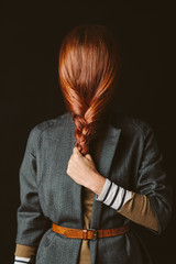 Woman hiding her face with a red braid