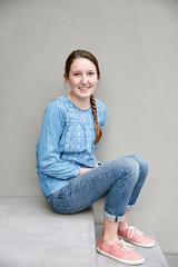 Portrait of teenage girl against grey wall