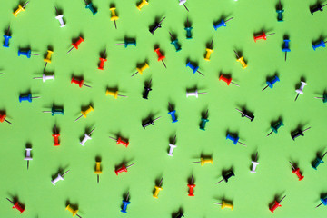 Colorful pins on green background
