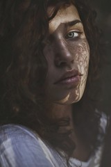 Beautiful young woman with curly hair, blue eyes and freckles looking in camera with shadows on her