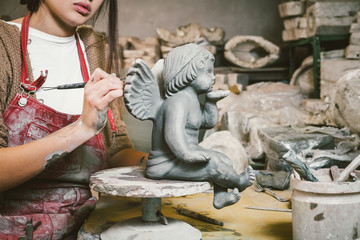 Young Artist Creating a Statue of an Angel with Ceramics