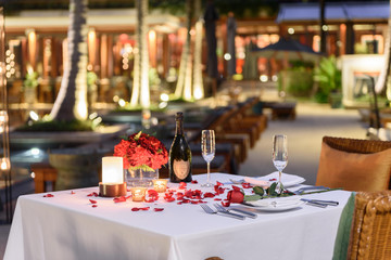 Special romantic candle light dinner table set up by the pool for couple with a bottle of champaign