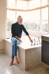 Mature woman relaxing in her luxury bathroom