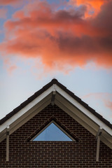 Light pink clouds in the rays of the sunset over the roof of the house.
