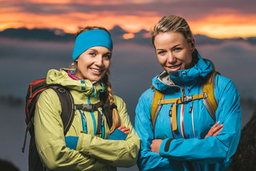 portrait of two beautiful blond sporty women in alpine scenery at sunset