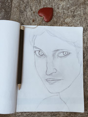 Sketch of woman face and pencil with heart seen from above
