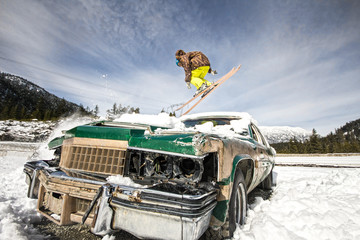 Ski freestyle - Skier jumping over old abandoned racing car