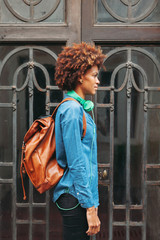 Profile portrait of afro american woman with leather backpack and green headphones in outdoors.