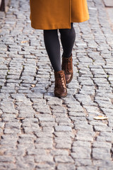 Closeup of legs of a young woman walking on the street