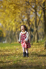 lovely little girl playing in the autumn ginkgo woods
