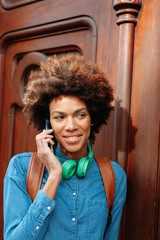 Afro american woman talking with phone on wood door.