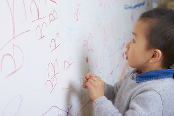 little boy drawing picture on the wall