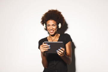 Young african american woman listening music on digital tablet against white background.