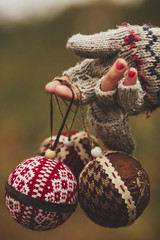 Hand in Glove Holding Christmas Ornaments