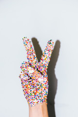 Woman making peace sign with sprinkles on her hand