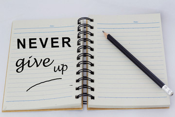 Motivational words NEVER GIVE UP written on one page of an opened notebook with pencil beside it.