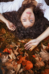 Beautiful young woman with curly hair, blue eyes and freckles lying on the leaves