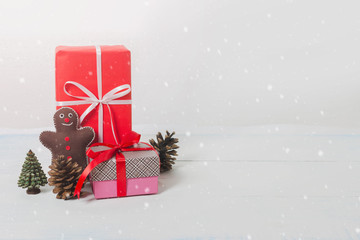 Christmas and New Year holidays gift box with decorative ornament on white wooden table with falling snow effect and copy space background.Gifts and congratulations concept.