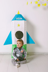 Child wearing handmade astronaut uniform sitting in front a diy rocket.
