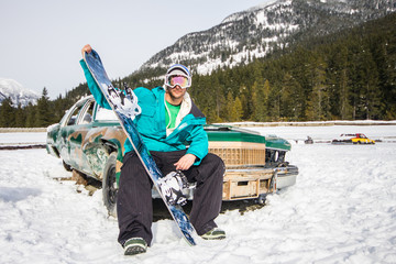 Snowboarder portrait sitting on an old vintage car on snow covered mountain landscape