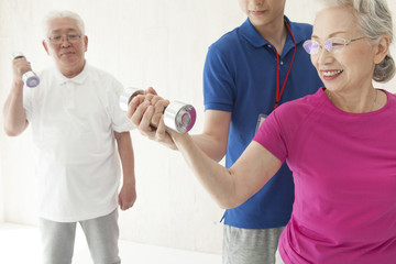 An elderly couple training dumbbell training with a trainer