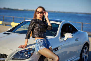 sexy girl in a leather jacket, denim shorts and black pantyhose in a grid stands near the car