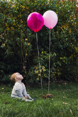 Cute readhead baby boy, playing with balloons outdoors