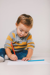 Cute child painting with color pencils on paper in the floor.