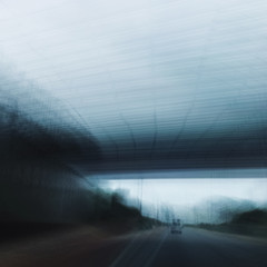 Intentional camera movement shot of car travelling under a bridge along a deserted road