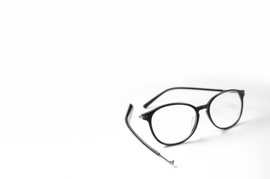 Old glasses on broken legs on white background,selective focus