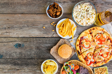Fast food on old wooden background. Concept of junk eating. Top view.