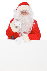 Santa Claus pointing on blank white wall, advertisement banner with copy space. Isolated on white background