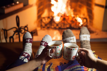 A man and a woman in front of a fireplace in warm socks. New Year. Christmas.