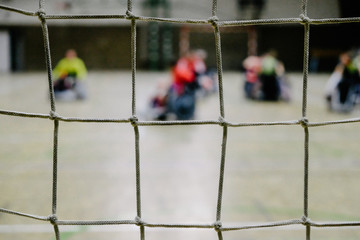 Net with defocused wheelchair rugby players in the background