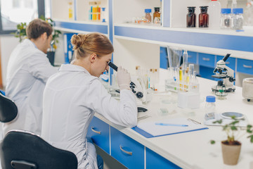 scientists with microscopes in laboratory