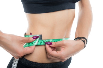 Close-up of fit girl abs measuring with tape