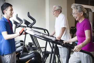 An old couple enjoying running machines with trainers