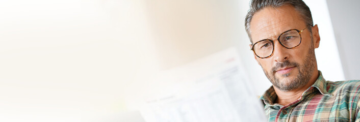 Mature man with eyeglasses reading newspaper- template