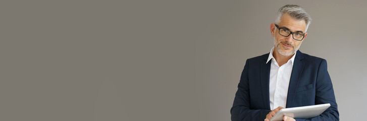 Obraz Trendy businessman using tablet, isolated - fototapety do salonu