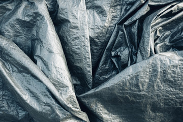 Closeup of silver tarpaulin covering pile of commercial fishing equipment